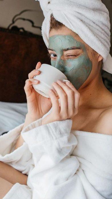 Chica bebiendo té, guiñando el ojo y llevando una mascarilla de arcilla verde