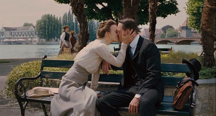 Escena de la película Un método peligoroso, pareja de lso años 30 sentada en una banca del parque besándose