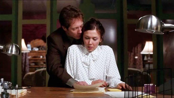 Escena de la película Secretary con Maggie Gyllenhall llevando camisa blanca con puntos negros