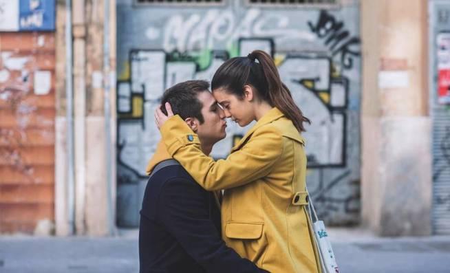 Escena de la película Amar, un chico abrazando a su novia con sao amarillo frente a una bodega