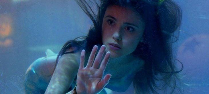 Poppy Drayton como sirena dentro de una pecera gigante en la película La sirenita del 2018
