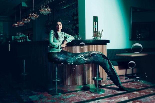 Escena de la serie de sirenas The Lure con una sirena sentada sobre los bancos de un bar