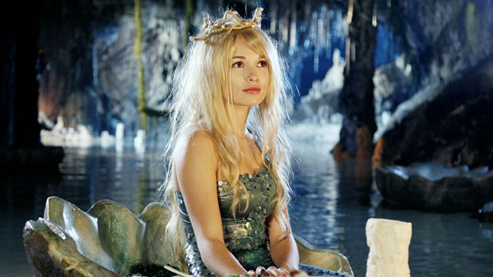 Escena de la película alemana Die kleine Meerjungfrau, una sirena debajo de una cueva llevando una corona de perlas