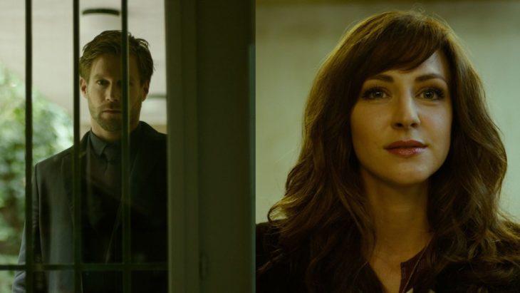 Escena de la serie El perfume, mujer mirando a través d euna ventana siendo espiada por un hombre
