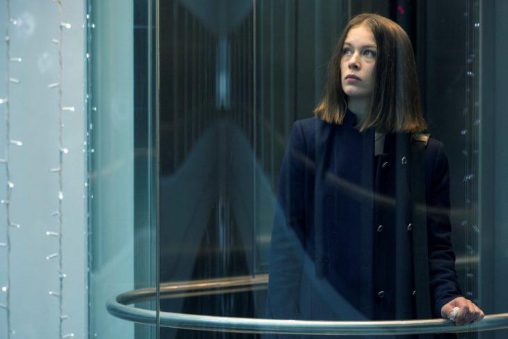 Escena de la serie alemana Bad Banks, una mujer mirando a través d eun vidrio por un pasillo largo