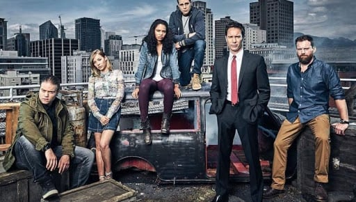 Escena de la serie Skylines, grupo de amigos reunidos frente a cientos de edificios, posando para una fotografía grupal