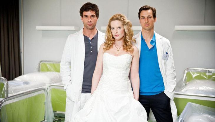 Escena de la serie alemana Diario de una doctora, mujer con vestido de novia posando junto a dos médicos dentro de un consultorio