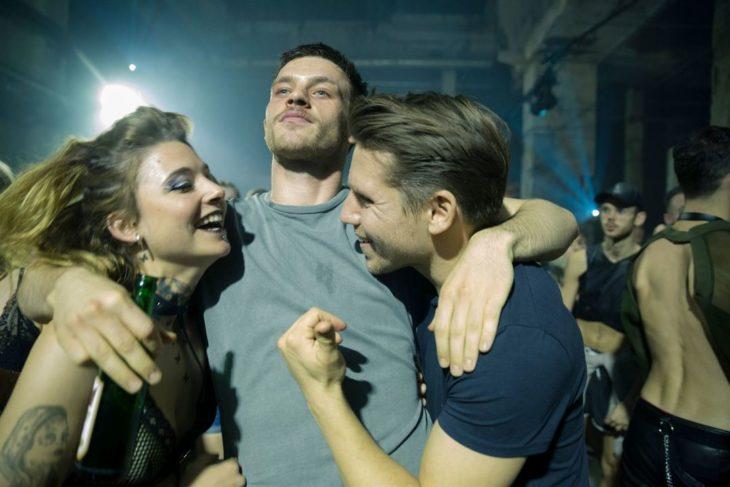 Escena de la serie Beat, amigos abrazados dentro de un bar