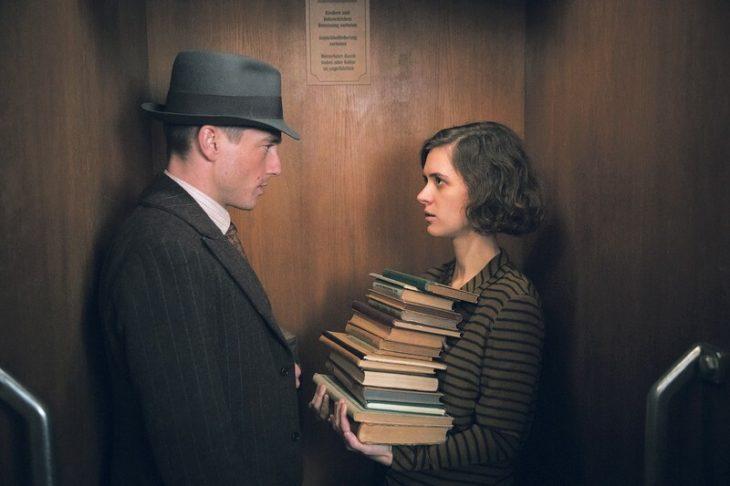 Escena de la serie alemana Babylon Berlin, un hombre y una mujer sosteniendo libros dentro de un elevador