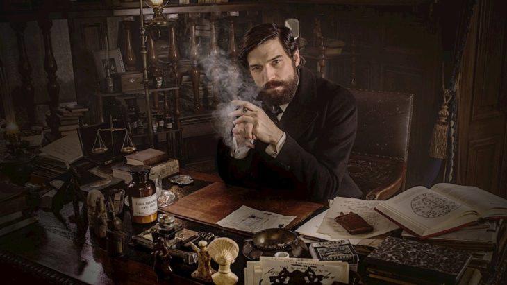 Escena de la serie alemana Freud, con Sigmund Freud sentado frente a un escritorio y fumando un puro