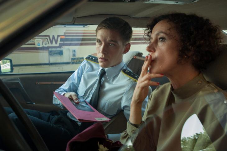 Escena de la serie Deutschland 83, mujer y un hombre fumando dentro de un automóvil, espiando a su alrededor