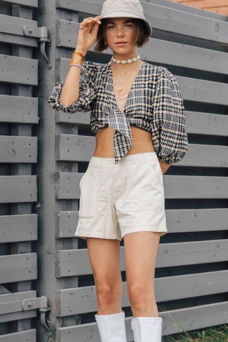Chica con short blanco, crop-top a cuadros y un sombrero estilo pescador