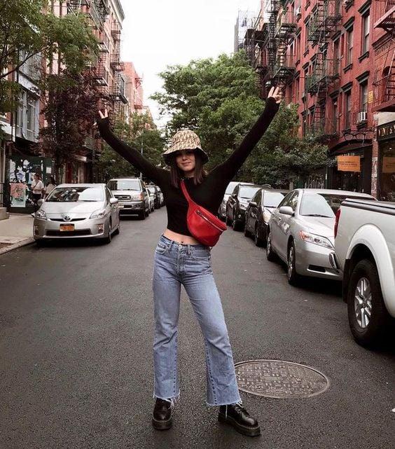 Chica parada a mitad de avenida llevando jeans de mezclilla, camisa negra y gorro estilo pescador