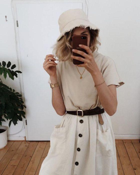 Chica tomando una selfie frente al espejo llevando un gorro estilo pescador