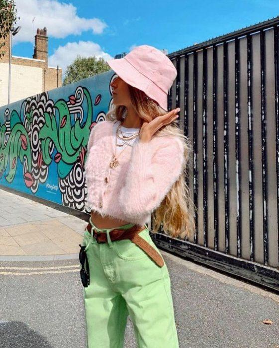 Chica posando para una foto en plebna avenida junto a una pared llena de dibujos