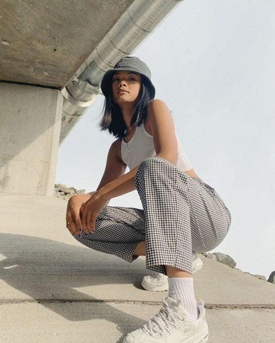 Chica bajo unas escaleras llevando un pantalón a cuadros y un gorro negro estilo pescador