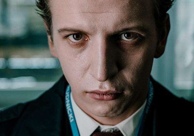 Escena de la serie The Hater, un chico con nariz larga y ceño fruncido , mirando hacia el frente con gesto molesto
