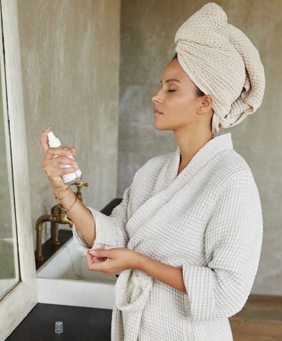 Mujer aplicando agua termal en su rostro