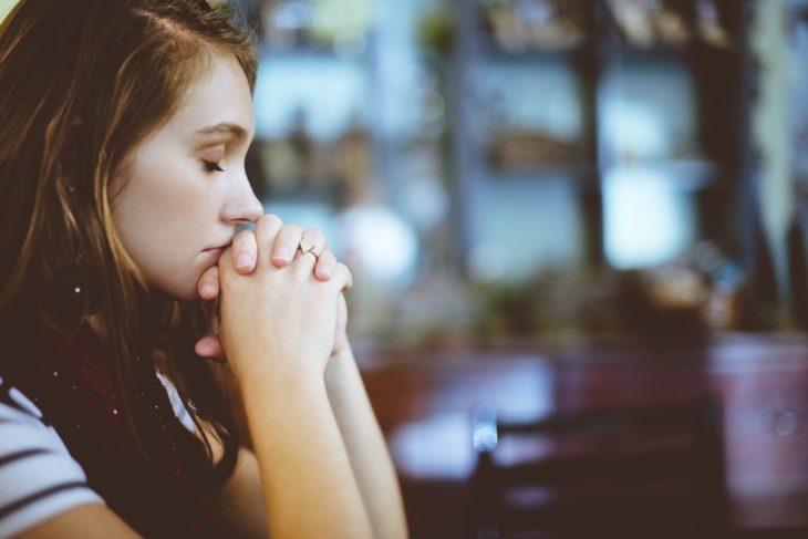 Chica pensando recargando el peso de su cabeza sobre sus manos