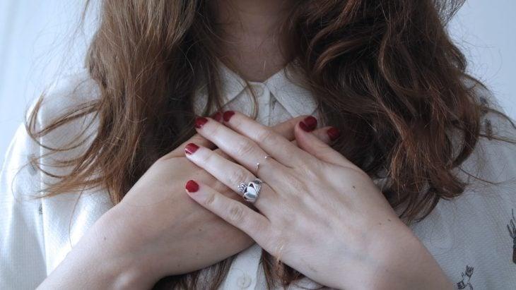 Chica con manos sobre su pecho