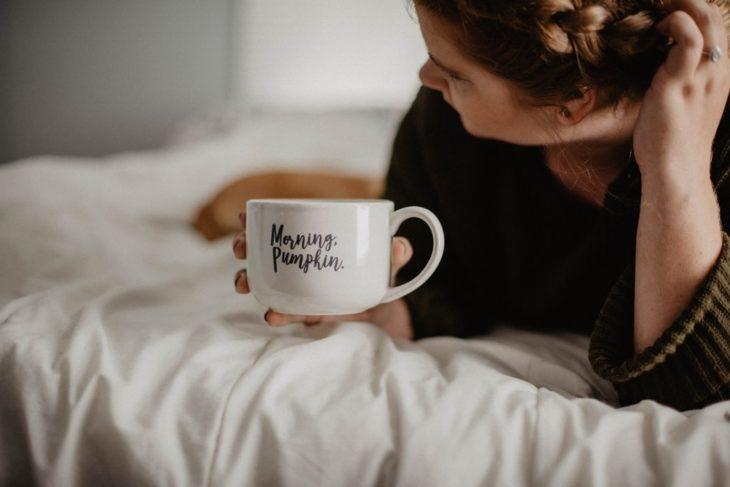 Mujer tomando café en un taza color blanca