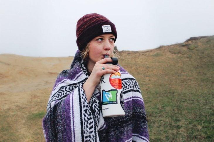 Chica bebiendo agua de un termo