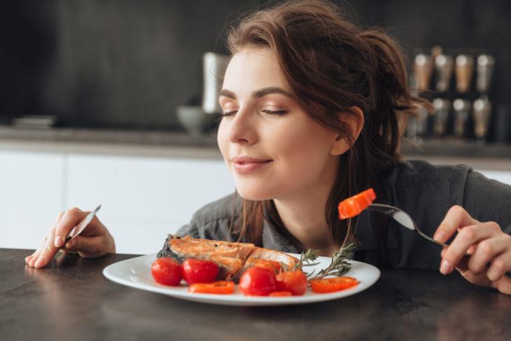chica comiendo salmón con tomates rojos
