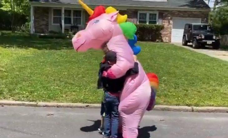 Nietos abarzando a su abuela disfrazada de unicornio