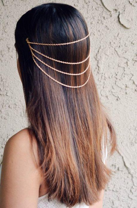 Chica de cabello largo y castaño con collar en el cabello