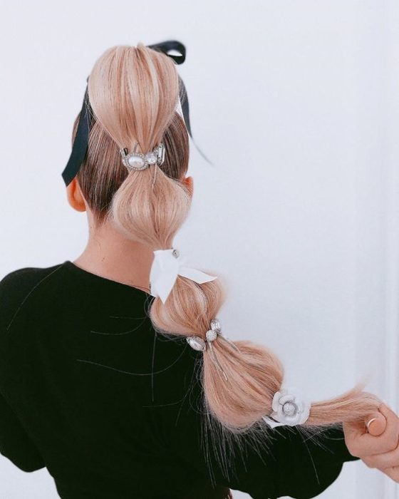 High ponytail with sections decorated with ribbons and pearls