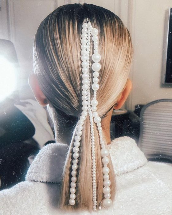 Polished low ponytail with pearls to the rear