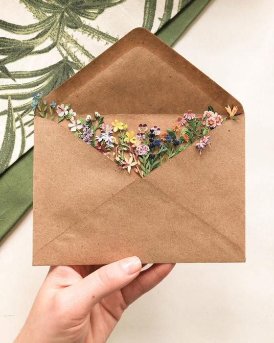 Miniramo de flores de papel de la artista Tania Lissova dentro de un sobre de cartoncillo café