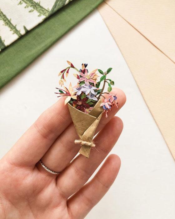 Miniramo de flores de papel de la artista Tania Lissova con tulipanes morados, azucenas envueltas en cartoncillo café,