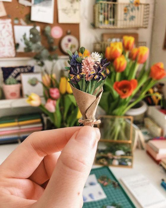Miniramo de flores de papel de la artista Tania Lissova con flores en tonso morados envuelta en un cartoncillo café