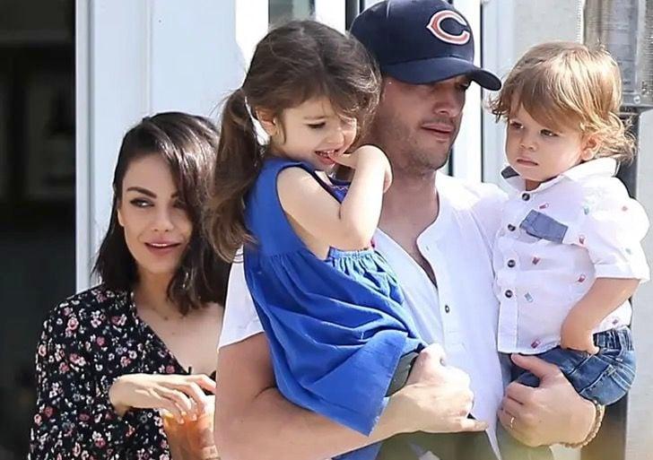 Ashton Kutcher cargando a sus dos hijos