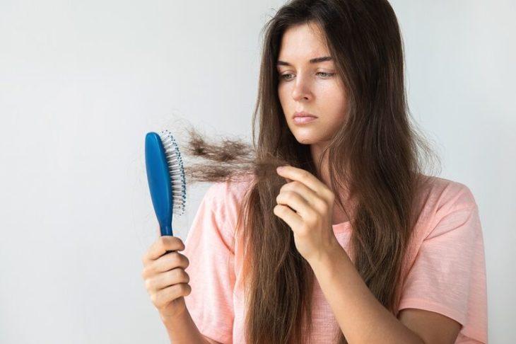 Chica sosteniendo un cepillo azul lleno de cabello