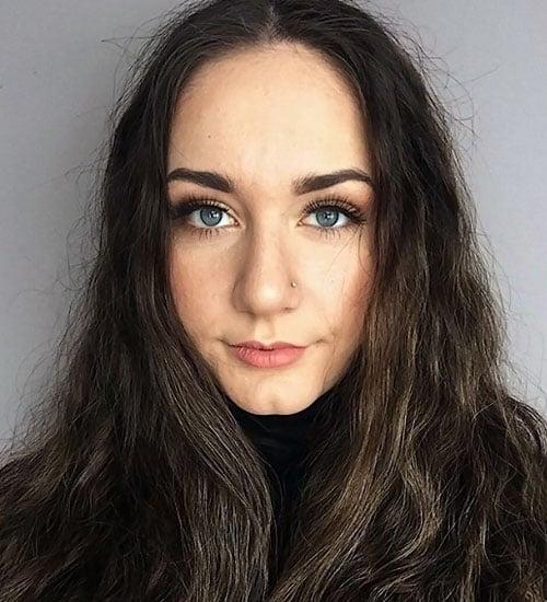 Mujer de ojos y cabello largo oscuro lleno de frizz