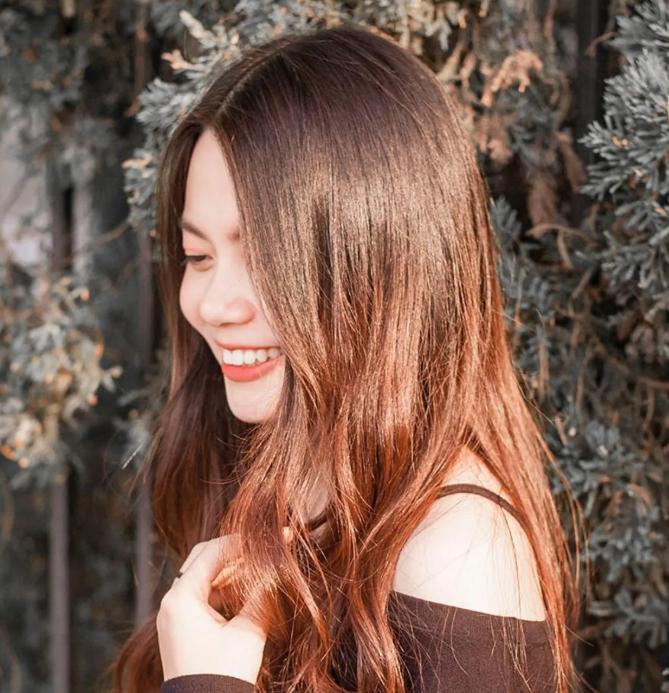 Chica sonriendo mientras toca su cabello largo brillante