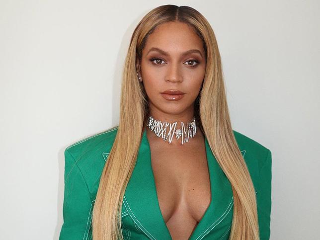Cantante Beyoncé vestida con chaqueta verde esmeralda y collar de brillantes
