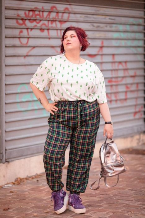 Curvy girl puts her hand on her waist and poses in a white cactus print blouse and green plaid pants