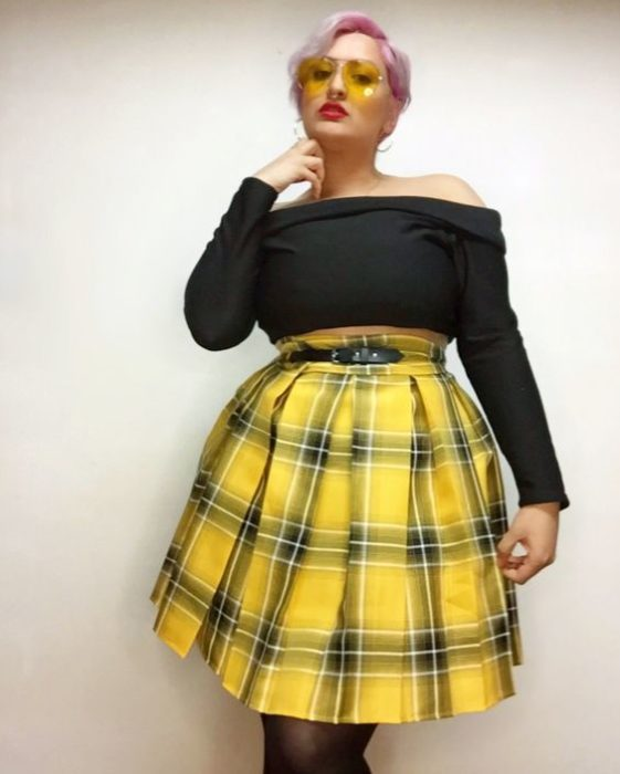 Plus size model poses in black off shoulder blouse and yellow plaid skirt