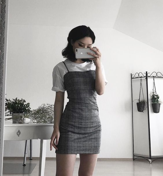 Girl takes a photo in front of the mirror in a white blouse and glued gray plaid dress