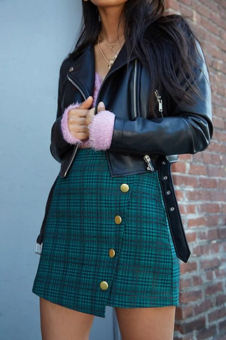 Girl wearing fur jacket, pink sweater and green plaid skirt