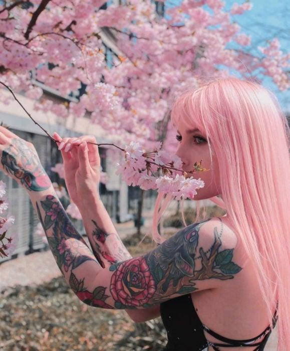 Cabello color rosa cherry blossom, flor de cerezo; mujer con tatuajes en los brazos junto a un árbol de flores rosas, cabello lacio y largo