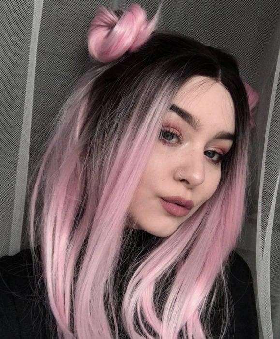 Cabello color rosa cherry blossom, flor de cerezo; chica de ojos verdes, concabello lacio y largo, peinado con chonguitos altos, perforación en la nariz