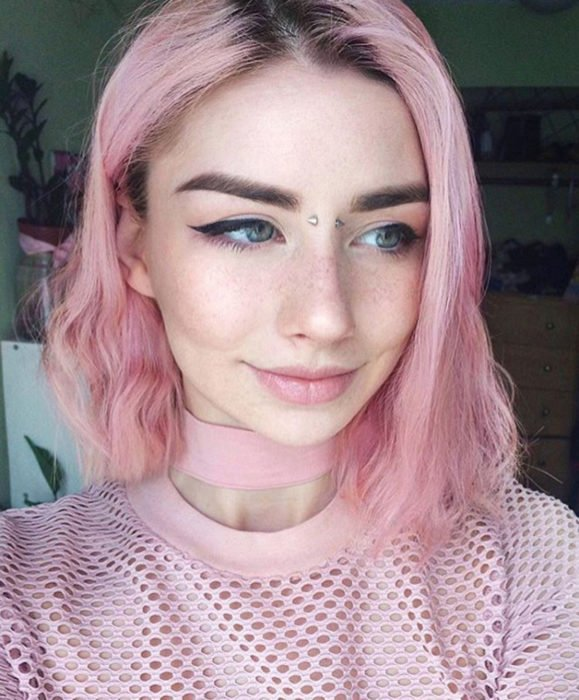 Cabello color rosa cherry blossom, flor de cerezo; mujer de ojos verdes con perforación en el puente de la nariz