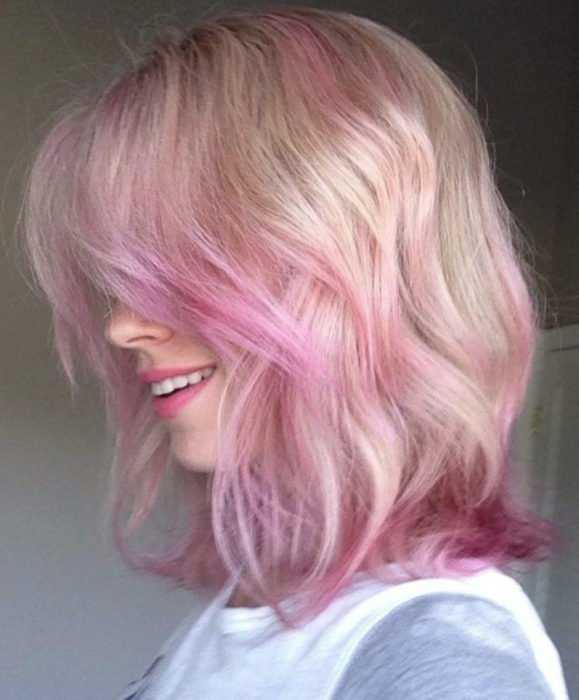 Cabello color rosa cherry blossom, flor de cerezo; mujer de perfil sonriendo, con cabello rubio y teñido en las puntas