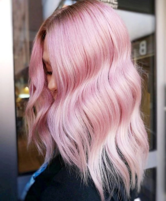 Cabello color rosa cherry blossom, flor de cerezo; mujer de cabello teñido, largo y ondulado
