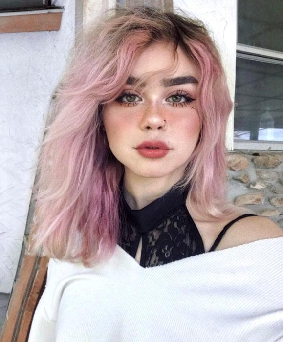 Cabello color rosa cherry blossom, flor de cerezo; chica de ojos verde con cabello despeinado hasta los hombros, perforación en la nariz