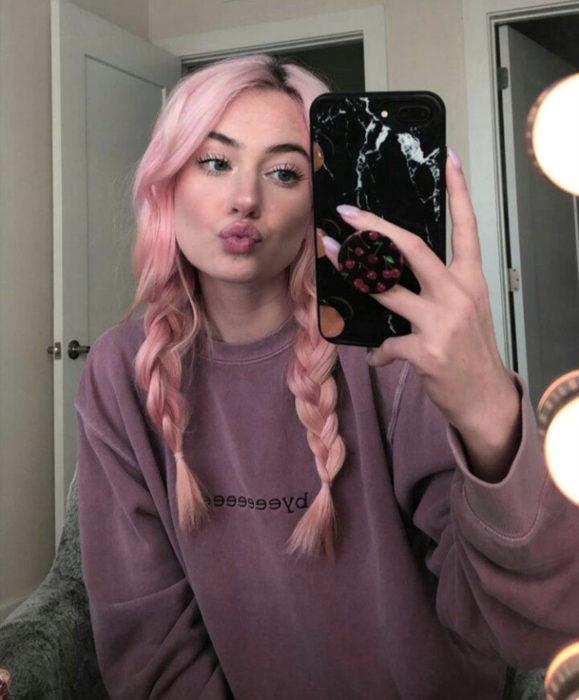 Cabello color rosa cherry blossom, flor de cerezo; chica tomándose selfie frente al espejo, con cabello peinado con trenzas, duck face